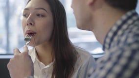 Porträt von jungen Paaren im modernen Café, welches zusammen die Zeit nah oben genießt Unerkennbarer Mann, der seine Freundin ein stock video footage
