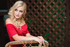 Porträt von jungen schönen gebräunten Blondinen im roten Glättungskleidersitzen im Freien im Straßencafé allein stockfotografie