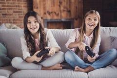 Porträt von zwei netten süßen hübschen reizenden attraktiven reizend lustigen netten positiven Mädchen, die auf dem Diwanspielen  lizenzfreie stockbilder
