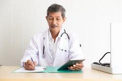 Porträt ältere Doktorkontrollmedizinischen Informationen lizenzfreie stockfotografie