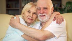 Porträt älteren Paaren von den im Ruhestand, die zu Hause auf dem umarmenden Sofa sitzen Immer währende große Liebe des Konzeptes stock footage