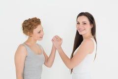 Porträt Armdrücken mit zwei des zufälligen jungen Freundinnen Lizenzfreie Stockfotografie