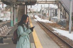 Porträt-Asiatinreisender, der auf Bahnhof steht und ihren Smartphone spielt lizenzfreie stockfotografie
