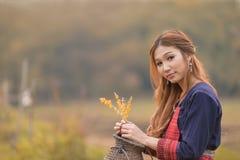 Porträt asiatischer langhaariger junger Dame im Stammkleid sitzen nahe Schalter lizenzfreies stockfoto