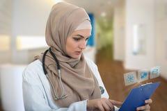 Porträt besorgten moslemischen weiblichen Arztes, der Papierklammer im Krankenhaus hält Lizenzfreie Stockfotografie
