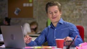 Porträt blonden Geschäftsmannes des von mittlerem Alter, der auf Laptop im Büro schreibt, stützt auf einen Stuhl und einen Geträn stock video footage