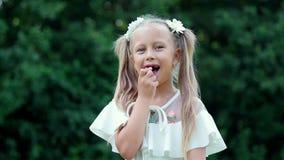 Porträt Blondes Mädchen, Kind, sitzend unter Gänseblümchen, in einer Wiese Ihr Haar wird mit Gänseblümchen verziert Sie lächelt u stock footage