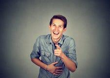 Porträt, das den jungen Mann zeigt mit dem Finger lacht Stockfotos