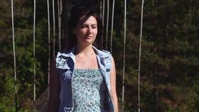 Porträt Das Mädchen geht entlang die Seilbrücke und betrachtet schön den Seiten stock video footage