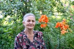 Porträt der älteren Frau in einem Garten Stockfotos