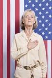 Porträt der älteren Frau mit überreichen Herz gegen amerikanische Flagge Stockfotos
