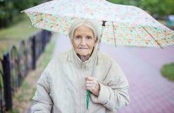 Porträt der älteren Frau unter Regenschirm stockfotos