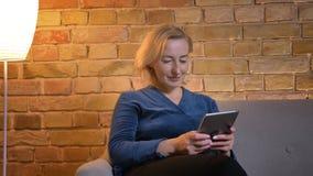 Porträt der älteren kaukasischen Frau, die auf Sofa sitzt und aufmerksam in Tablette in der gemütlichen Hauptatmosphäre aufpasst stockfotografie