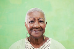 Porträt der älteren schwarzen Frau, die an der Kamera auf grünem backgr lächelt Stockfotografie