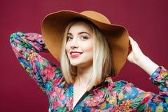Porträt der überraschenden Blondine mit dem langen Haar und dem Hut, welche die Kamera betrachtet und auf rosa Hintergrund im Stu Stockfotografie