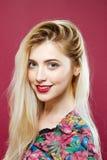 Porträt der überraschenden Blondine mit dem langen Haar, welches die Kamera betrachtet und auf rosa Hintergrund im Studio lächelt Lizenzfreie Stockbilder