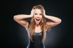 Porträt der überraschten Frau über dunklem Hintergrund Lizenzfreies Stockfoto
