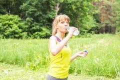 Porträt der überraschten jungen Eignungsfrau, die an der Wasserflasche trinkt Stockfotografie