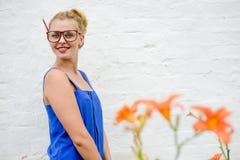 Porträt der überraschten jungen Frau in den Gläsern mit den orange Blumen, die über weißem Ziegelsteinhintergrund stehen Stockfoto