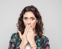 Porträt der überraschten jungen Frau gegen grauen Hintergrund stockfoto