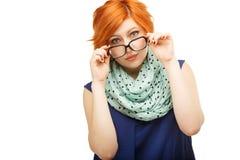 Porträt der überraschten rothaarigen jungen Frau, die an Gläser hält stockbilder