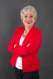 Porträt der überzeugten älteren Frau in der roten Jacke Stockbilder