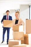 Porträt der überzeugten jungen Geschäftsfrau, die Staplungskästen mit männlichem Kollegen im Hintergrund im Büro bereitsteht Lizenzfreie Stockfotos