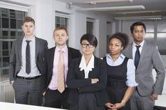 Porträt der überzeugten jungen multiethnischen Geschäftsgruppe im Büro stockbilder