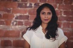 Porträt der überzeugten jungen weiblichen Berufsstellung an der Kaffeestube lizenzfreie stockbilder
