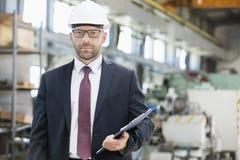 Porträt der überzeugten mittleren erwachsener Mannesaufsichtskraft, die Klemmbrett in der Metallindustrie hält stockfotos