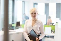 Porträt der überzeugten reifen Geschäftsfrau mit Datei im Büro Stockfotos