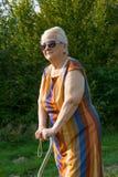 Porträt der alten Frau aufwerfend mit einem Stock Lizenzfreies Stockfoto