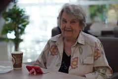 Porträt der alten lächelnden Frau im Café Lizenzfreies Stockbild