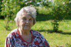 Porträt der alten lächelnden Frau im gargen Stockfotografie