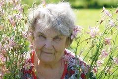 Porträt der alten lächelnden Frau im Park Stockfotos