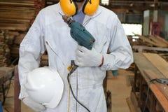 Porträt der Arbeitskraft mit einheitlicher haltener elektrischer Bohrmaschine der Sicherheit in der Zimmereiwerkstatt lizenzfreie stockfotografie