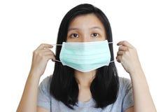 Porträt der Asiatin setzend auf medizinische Maske auf weißem Hintergrund Stockfotos