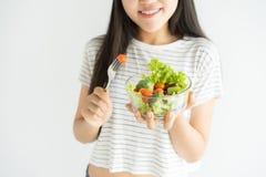 Porträt der asiatischen Frau zu Hause lächelnd und Salat auf weißem Hintergrund, Nahrung für Gesundheitswesen und Diät essend stockfoto