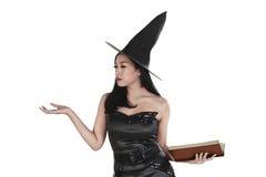 Porträt der asiatischen Hexenfrau mit Buch und offener Palme Lizenzfreie Stockfotografie