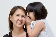 Porträt der asiatischen Mutter flüsternd zu ihrer Tochter Stockfotos
