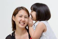 Porträt der asiatischen Mutter flüsternd zu ihrer Tochter Lizenzfreies Stockbild
