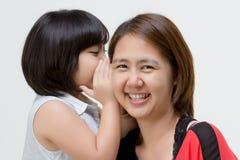 Porträt der asiatischen Mutter flüsternd zu ihrer Tochter Lizenzfreie Stockfotos