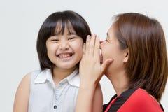 Porträt der asiatischen Mutter flüsternd zu ihrer Tochter Lizenzfreie Stockbilder
