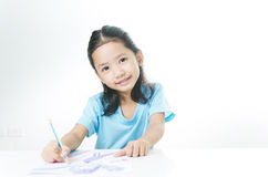 Porträt der asiatischen Zeichnung des kleinen Mädchens des Lächelns mit Farbbleistift Lizenzfreie Stockfotografie