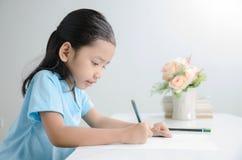 Porträt der asiatischen Zeichnung des kleinen Mädchens mit Bleistift Lizenzfreies Stockbild