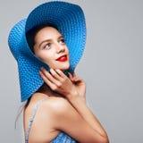 Porträt der attraktiven eleganten Frau im blauen Hut und im Kleid Stockbilder