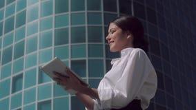Porträt der attraktiven erfreuten Geschäftsfrau, die gegen Geschäftszentrumhintergrund steht und an ihrer Tablette arbeitet stock video footage