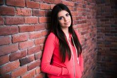 Porträt der attraktiven Frau lehnend auf der Backsteinmauer Stockbilder