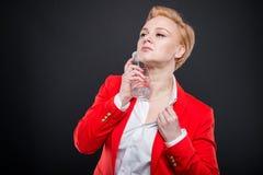 Porträt der attraktiven Geschäftsfrau, die mit Flasche wat abkühlt Lizenzfreie Stockfotos