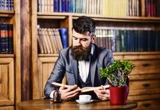 Porträt der attraktiven Geschäftsmannlesung am Arbeitsplatz Ausbildung und Bücher concep lizenzfreie stockfotos